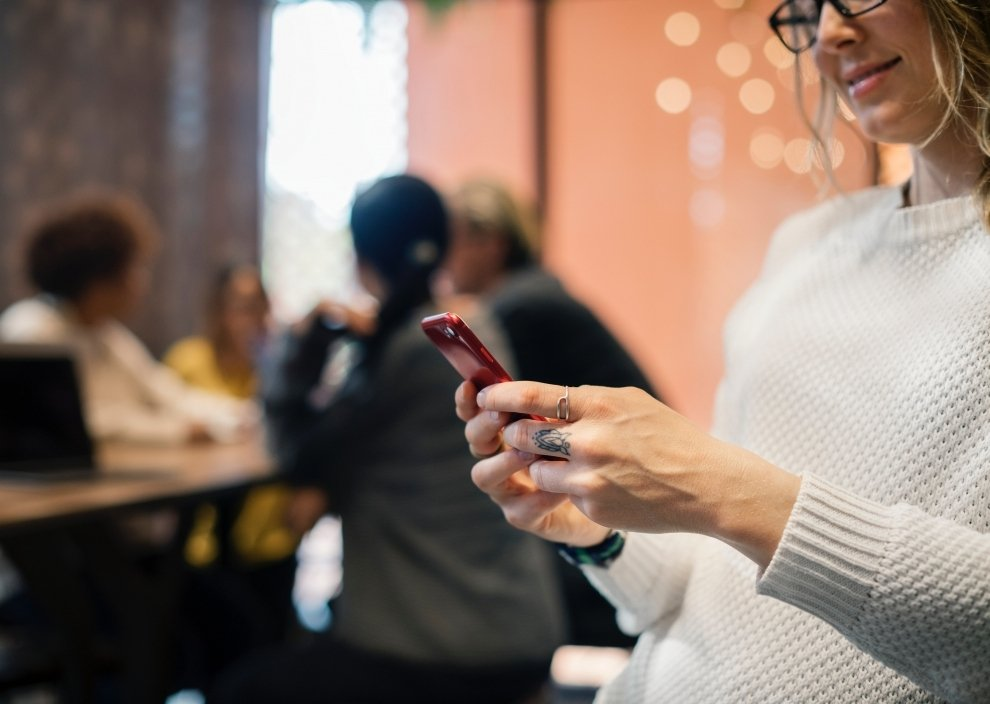Woman holding phone in white shirt at a cafe