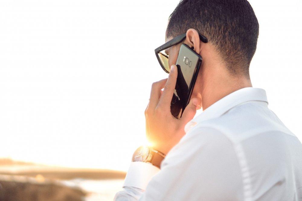 Man i solnedgång pratar i telefonen